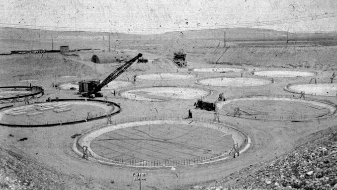 "FILE - This 1944 photo provided by the U.S. Department of Energy shows the construction of a ""tank farm"" to store nuclear waste on the Hanford Nuclear Reservation near Richland, Wash. The first 149 storage tanks at the Hanford Nuclear Reservation were built between 1943 and 1964 with just a single, stainless-steel wall. They were designed to last only 10 to 20 years, because they were intended as a stopgap measure until a more permanent solution could be found to deal with the waste. Turns out the tanks were susceptible to corrosion; some even buckled from the extreme heat radiated by the waste. Between 1959 and 1968, the U.S. Energy Department confirmed that 12 tanks were leaking. (AP Photo/U.S. Department of Energy, File)"