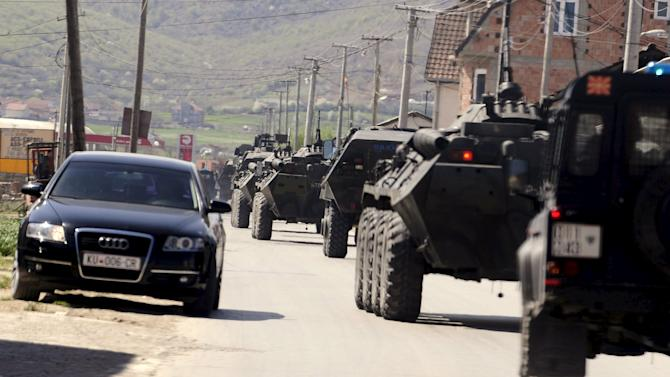 Police armed personnel carriers travel down a road to the village of Goshince from where police officers were taken hostage overnight, north of the capital Skopje
