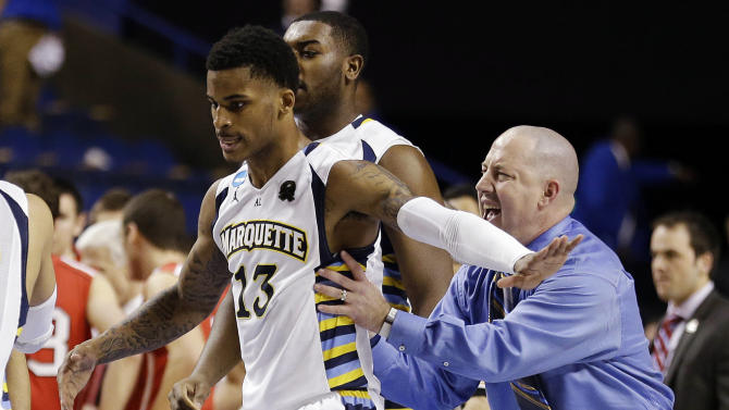 Marquette guard Vander Blue (13) and head coach Buzz Williams celebrate after Blue hit the winning basket against Davidson with one second left in their second-round NCAA college basketball tournament game, Thursday, March 21, 2013, in Lexington, Ky. Marquette won 59-58. (AP Photo/John Bazemore)