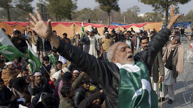CORRECTS YEAR - Supporters of Pakistani Sunni Muslim cleric Tahir-ul-Qadri, unseen, chant anti-government slogans gathered in Islamabad to receive their leader on Monday, Jan. 14, 2013 in Islamabad, Pakistan.   Thousands of supporters of the fiery cleric who has been calling for election reforms were descending Monday on the Pakistani capital, where authorities have put up barricades and sent riot police into the streets in preparation. (AP Photo/B.K. Bangash)