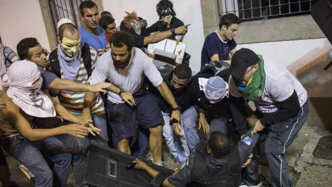 Some demonstrators try to help a police officer after he clashed with others during a protest near the state legislative assembly in Rio de Janeiro, Brazil, Monday, June 17, 2013. Officers in Rio fired tear gas and rubber bullets when a group of protesters invaded the state legislative assembly and threw rocks and flares at police. Protesters massed in at least seven Brazilian cities Monday for another round of demonstrations voicing disgruntlement about life in the country, raising questions about security during big events like the current Confederations Cup and a papal visit next month. (AP Photo/Felipe Dana)