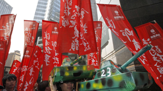 Protesters display mock Chinese PLA tanks during a demonstration against Beijing's involvement in Hong Kong's chief executive election outside a polling station in Hong Kong, Sunday, March 25, 2012. Hong Kong's elite voted Sunday to choose the city's next leader following a tumultuous, bitter race that highlighted public discontent in the southern Chinese financial hub. (AP Photo/Vincent Yu)