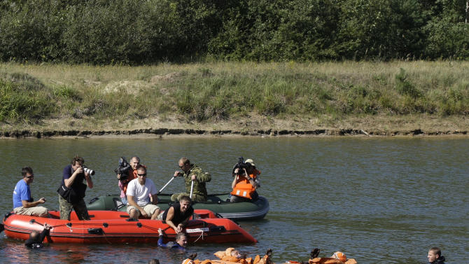 In the water in orange, members of an expedition to the International Space Station, US astronaut Karen Nyberg, right, Italian astronaut Luca Parmitano, left, and Russian cosmonaut Maxim Suraev train in  Noginsk, outside Moscow, Russia, Thursday, Aug. 18, 2011. (AP Photo/Misha Japaridze)
