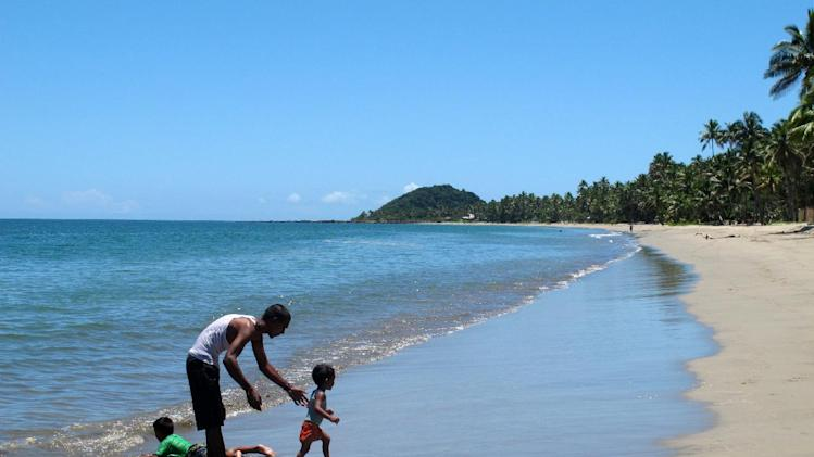 This Nov. 7, 2013 photo shows a man playing with children at Pacific Harbour Beach in Fiji. A fringe of coconut trees gives way to a gorgeous, pristine beach with a gentle arc. It's the perfect place for a swim in placid waters that are as warm as a bath. (AP Photo/Nick Perry)