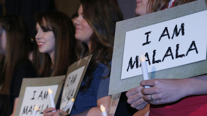 """Girls from 33 Oklahoma communities hold signs that read """"I am Malala"""" following the presentation of the Reflectons of Hope Award in Oklahoma City, Monday, May 13, 2013. The award was presented to Ziauddin Yousafzai and his daughter Malala Yousafzai, who was not present. Malala was shot in the head by a Taliban gunman in an assassination attempt that drew attention worldwide to the struggle for women's rights in her homeland. (AP Photo/Sue Ogrocki)"""