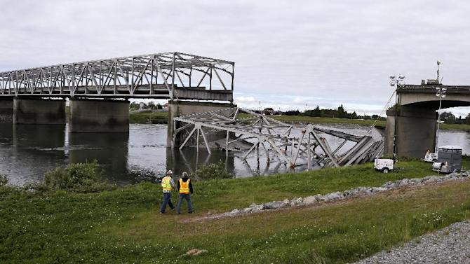 Workers walk past the collapsed portion of the Interstate 5 bridge at the Skagit River Friday, May 24, 2013, in Mount Vernon, Wash. A truck carrying an oversize load struck the four-lane bridge on the major thoroughfare between Seattle and Canada, sending a section of the span and two vehicles into the Skagit River below Thursday evening. All three occupants suffered only minor injuries. At an overnight news conference, Washington State Patrol Chief John Batiste blamed the collapse on a tractor-trailer carrying a tall load that hit an upper part of the span. (AP Photo/Elaine Thompson)