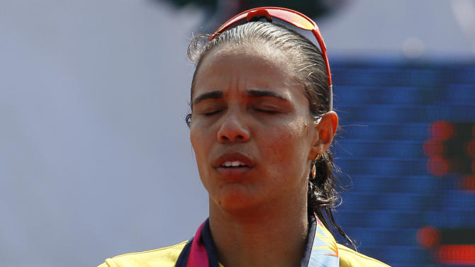 Gold medal winner Brazil's Juliana Silva sings her country's national anthem at the podium during the women's beach volleyball award ceremony at the Pan American Games in Puerto Vallarta, Mexico, Friday, Oct. 21, 2011. (AP Photo/Ariana Cubillos)