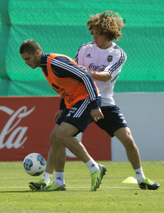 Argentina's Mauro Icardi, left, vies for the ball with Fabricio Coloccini at a team training session ahead a Brazil 2014 World Cup qualifying soccer match against Peru in Buenos Aires, Argentina, Tues