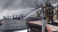 Firefighters work to douse flames on a boat that exploded in Oakville, according to police.