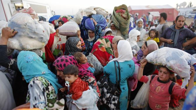 Newly arrived Syrian Kurdish refugees carry their belongings after crossing into Turkey near the southeastern town of Suruc