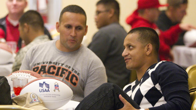 In this photo provided by IMG Consulting, Chris Walter, left, looks on as Guny Aragon, right, shows his wounded knee at Schofield Barracks Thursday, Jan. 24, 2013, in Honolulu. Both Walter and Aragon are members of the Warrior Transition Battalion. Both were wounded in action while serving their country in war. Members of the Warrior Transition Battalion participated in a luncheon and a autograph session with several NFL All-Stars that will be playing in this weekend's Pro Bowl. (Eugene Tanner/AP Images for USAA. IMG Consulting