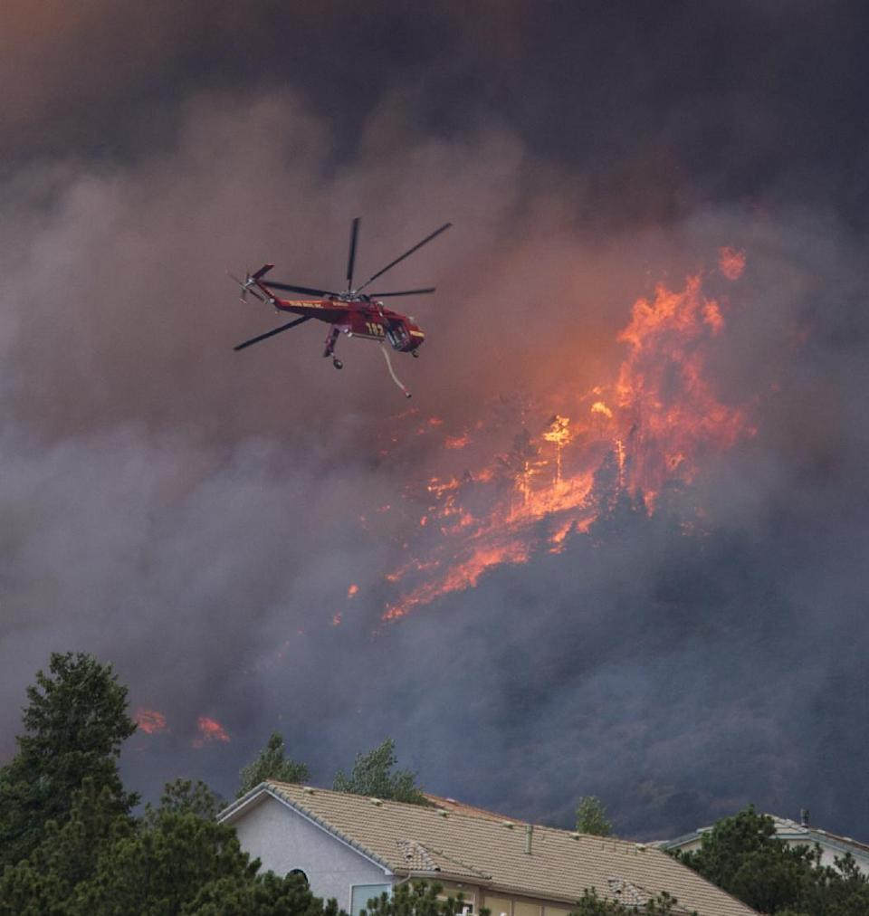 A helicopter tries to put out fire on the Waldo Canyon wildfire as it moved into subdivisions and destroyed homes in Colorado Springs, Colo., on Tuesday, June 26, 2012. (AP Photo/Gaylon Wampler)