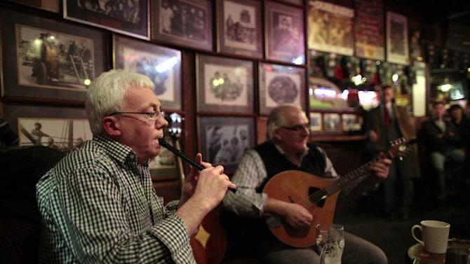 "This Feb. 19, 2013 photo shows Cian O'Sullivan, left, and Tom Walsh playing music in O'Donoghue's pub in central Dublin, Ireland. The most famous pub for live ""trad""' performances is O'Donoghue's, a living room-sized venue that inspired the Dubliners and Chieftains in the 1960s.   (AP Photo/Peter Morrison)"
