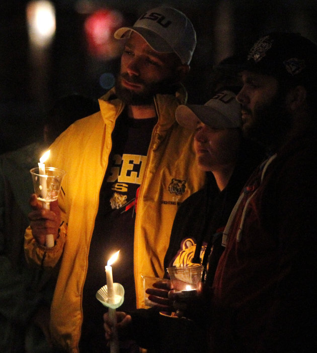 James Stephens, left, and Autumn, center, join others to pray for a 5-year-old boy taken hostage, in Midland City, Ala., Sunday, Feb. 3, 2013. Authorities say Jim Lee Dykes, 65 — a decorated Vietnam-e