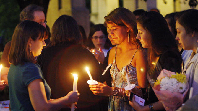 Boston University students including Tori Pinheiro, third right, of New Bedford, Mass., participate in a candlelight vigil on Marsh Plaza at Boston University, Saturday, May 12, 2012, in Boston, for three students studying in New Zealand who were killed when their minivan crashed during a weekend trip. Daniela Lekhno, 20, of Manalapan, N.J.; Austin Brashears, 21, of Huntington Beach, Calif.; and Roch Jauberty, 21, whose parents live in Paris, were killed as they traveled in a minivan Saturday. (AP Photo/Bizuayehu Tesfaye)