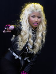 FILE - In this Saturday, June 23, 2012 file photo, singer Nicki Minaj performs on stage at the Radio One Hackney Music Festival in Hackney marshes, east London. Nicki Minaj has canceled her appearance at this weekend's V Festival in the United Kingdom because of damage to her vocal chords, Saturday, Aug. 18, 2012. (AP Photo/Joel Ryan, File)