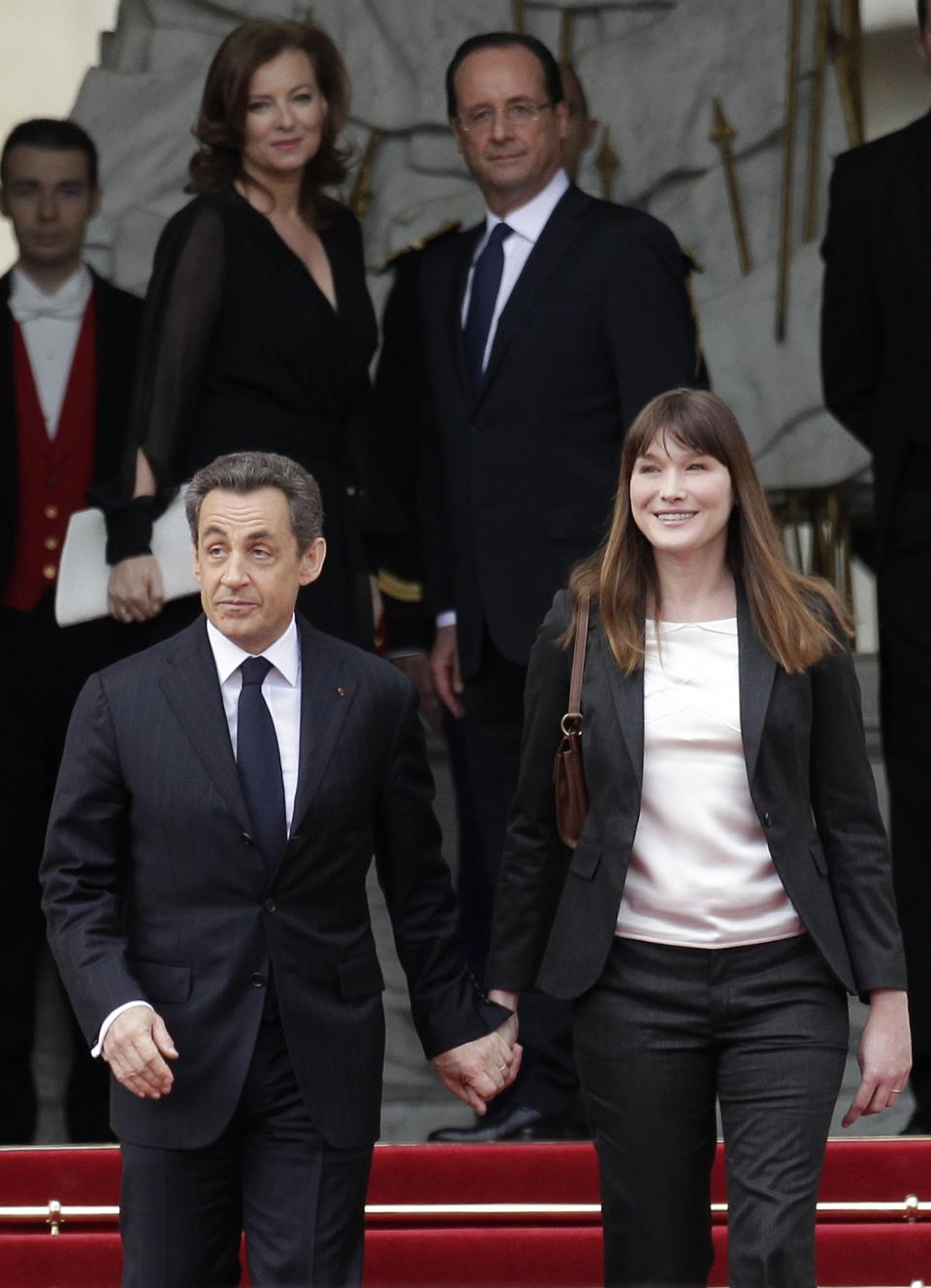 Outgoing French President Nicolas Sarkozy and his wife Carla Bruni-Sarkozy leave the Elysee Palace after the handover ceremony while new President Francois Hollande, top right, and his companion Valerie Trierweiler look on, Tuesday, May 15, 2012 in Paris.  (AP Photo/Michel Euler)
