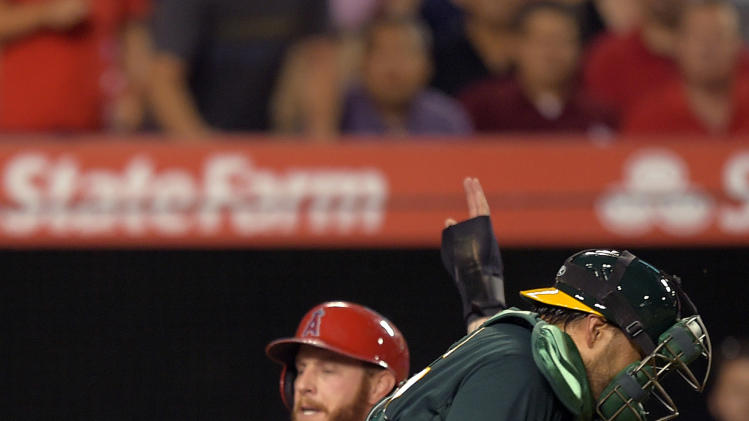 Los Angeles Angels' Josh Hamilton, left, scores on a single by Erick Aybar as Oakland Athletics catcher Geovany Soto takes a late throw during the second inning of a baseball game, Thursday, Aug. 28, 2014, in Anaheim, Calif. (AP Photo/Mark J. Terrill)