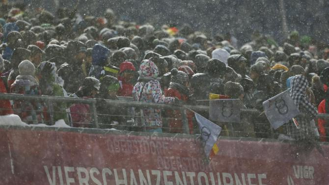 Spectators wait for the start of the first jumping of the 63rd four-hills ski jumping tournament in Oberstdorf