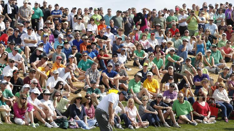 Phil Mickelson chips to the sixth green as a large gallery watches from behind during the third round of the Waste Management Phoenix Open golf tournament, Saturday, Feb. 2, 2013, in Scottsdale, Ariz. (AP Photo/Matt York)