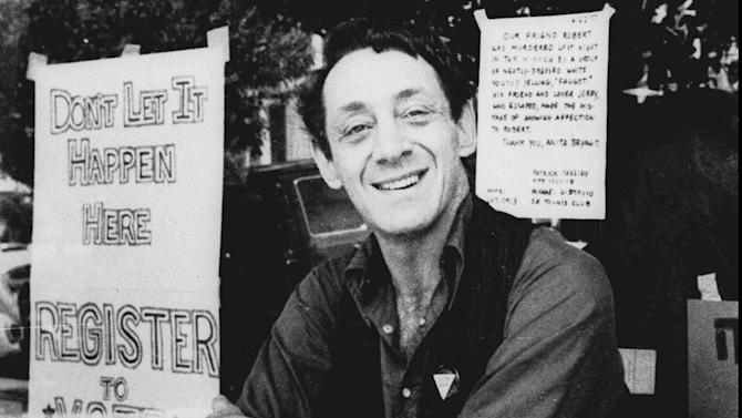 FILE - In a Nov. 9, 1977 file photo, Harvey Milk poses in front of his camera shop in San Francisco. A charter amendment sponsored by city Supervisor David Campos on Tuesday, Jan. 15, 2013 planned to introduce legislation asking voters to rename the city's airport after slain gay rights leader Harvey Milk. The amendment would put the question of creating Harvey Milk-San Francisco International Airport on San Francisco's November ballot. Milk became one of the first openly gay men elected to public office in the United States when he won a seat on the board of supervisors in 1977. He was assassinated at City Hall, along with Mayor George Moscone, more than a year later.   (AP Photo, File)
