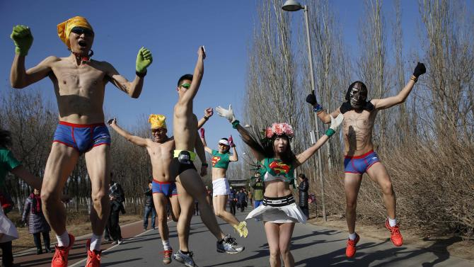 "Participants jump as they run in the ""Half-Naked Marathon"" at a park in Beijing"