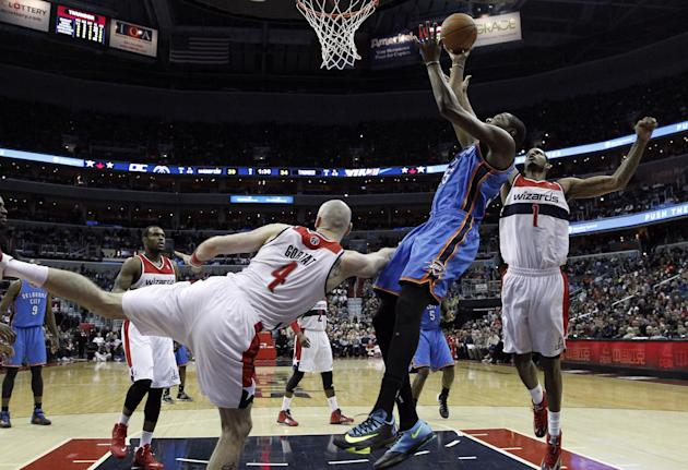 Oklahoma City Thunder forward Kevin Durant, front right, shoots as he is defended by Washington Wizards center Marcin Gortat (4), from Poland, and forward Trevor Ariza (1) in the first half of an NBA