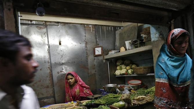 A vendor waits for customers at her shop selling vegetables in Dharavi in Mumbai