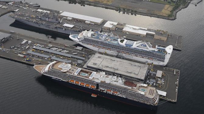 In this aerial photo taken Aug. 2, 2014, in Seattle, cruise ships from Princess Cruise Lines, top, and Holland America Line, bottom, are shown docked near downtown Seattle. (AP Photo/Ted S. Warren)