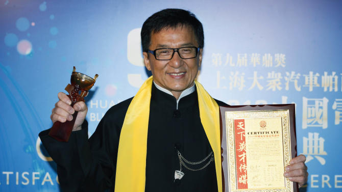 """FILE - In this Wednesday, April 10, 2013 file photo, Hong Kong movie star Jackie Chan poses after winning the Best Action Movie in China Award at the Huading Awards in Hong Kong. Chan has received a lot of awards during a career that's spanned 50 years. But a best director award is rare on his trophy shelves. The action star took home one Wednesday night for his 100th film, """"Chinese Zodiac."""" (AP Photo/Kin Cheung, File)"""