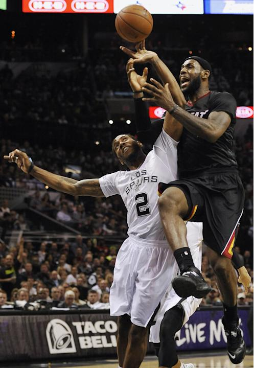 Miami Heat forward LeBron James, right, is fouled by San Antonio Spurs forward Kawhi Leonard during the second half of an NBA basketball game on Thursday, March 6, 2014, in San Antonio. San Antonio wo