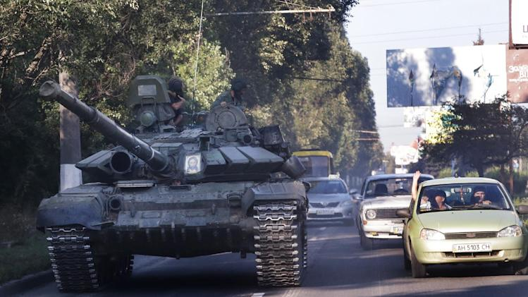 Pro-Russian rebels ride on a tank near the town of Makeyevka, eastern Ukraine, Saturday, Aug. 23, 2014. Hundreds of Russian aid trucks returned home from rebel-held eastern Ukraine on Saturday, highlighting a dire need for long-term assistance to the region where homes and livelihoods have been destroyed by months of fighting. (AP Photo/Sergei Grits)