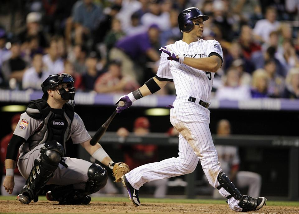 Colorado Rockies' Carlos Gonzalez hits a solo home run in front of Houston Astros catcher Chris Snyder in the fifth inning of a baseball game, Wednesday, May 30, 2012, in Denver. (AP Photo/Joe Mahoney)