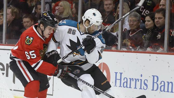 Chicago Blackhawks center Andrew Shaw (65) and San Jose Sharks center Michal Handzus (26), from Slovakia, race for the puck during the first period of an NHL hockey game Friday, Feb. 15, 2013, in Chicago. (AP Photo/Charles Rex Arbogast)