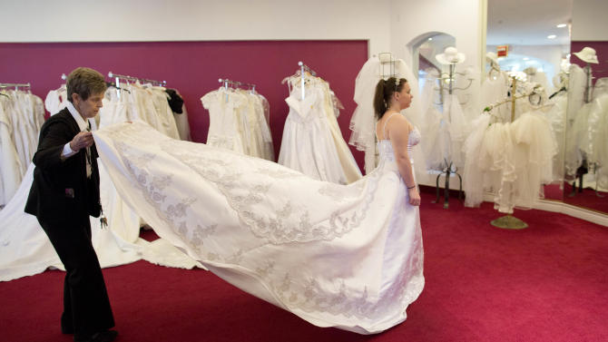 "In preparation for her Dec. 12 wedding, Bethany Wood of Jackson, Mich., tries on a wedding gown with the help of Linda de Marre, Tuesday, Dec. 11, 2012, at A Little White Wedding Chapel in Las Vegas. These ""once-in-a-century"" wedding dates have become more important each year as people increasingly look outside of Vegas for nontraditional wedding. Once known as the wedding capital of the world, Vegas' share of the U.S. wedding market has fallen by a third since 2004. (AP Photo/Julie Jacobson)"