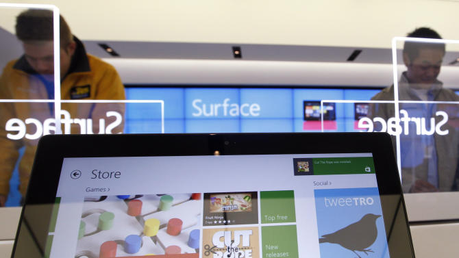 Customers look at new Microsoft Surface tablet computers Friday, Oct. 26, 2012, at a Microsoft store in Seattle. Friday was the first day of sales for the new Windows 8 operating system and the company's new tablet computer, the Surface. (AP Photo/Elaine Thompson)