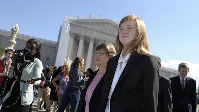 Abigail Fisher, right, who sued the University of Texas, walks outside the Supreme Court in Washington, Wednesday, Oct. 10, 2012. The Supreme Court is taking up a challenge to a University of Texas program that considers race in some college admissions. The case could produce new limits on affirmative action at universities, or roll it back entirely. (AP Photo/Susan Walsh)