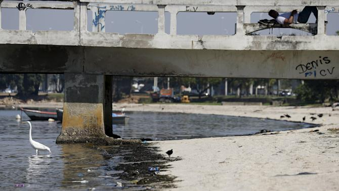A man relaxes on Sao Bento beach at Guanabara Bay, which receives waters from polluted rivers in Rio de Janeiro