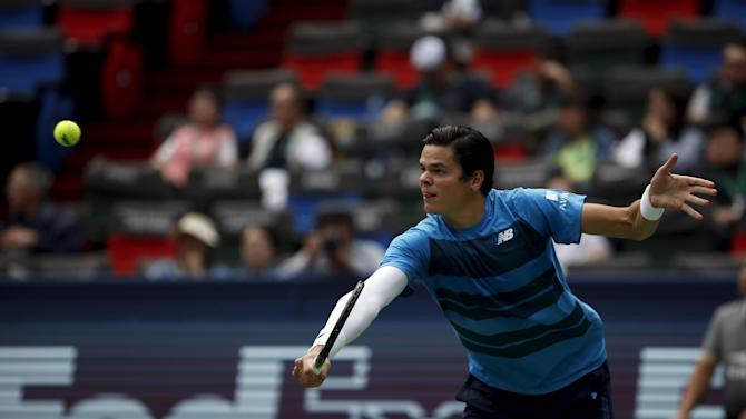Milos Raonic of Canada returns a shot to Thomaz Bellucci of Brazil during their men's singles match at the Shanghai Masters tennis tournament in Shanghai