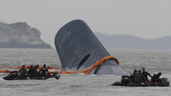 FILE - In this April 17, 2014 file photo, South Korean Coast Guard officers search for missing passengers aboard sunken ferry Sewol in the waters off the southern coast near Jindo, South Korea. The anger, grief and deep remorse at Danwon High School in Ansan, outside of Seoul, was a reflection of what many South Koreans have felt since the April 16 sinking of the ferry that left more than 300 people dead or missing. Of the 325 students on a class trip to the southern holiday island of Jeju, 75 were rescued, 245 died and 5 are still missing. Two of those rescued had already returned to school, officials said. (AP Photo/Ahn Young-joon, File)