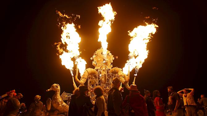 Participants gather to watch the flames from the art car El Popo Mechanico during Burning Man 2015 in the Black Rock Desert of Nevada