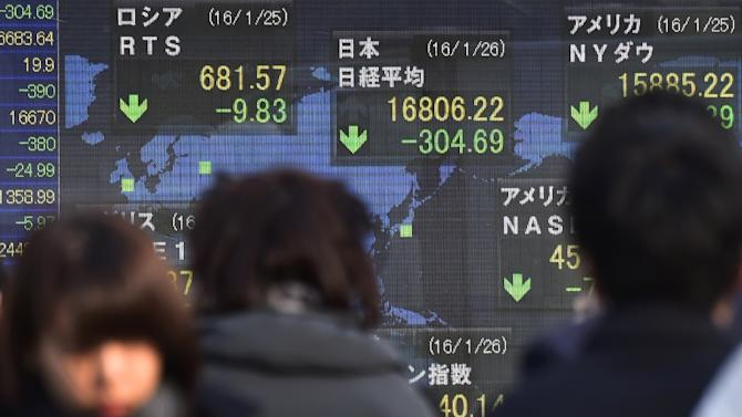 Pedestrians walk past a share prices board displaying movements on the Tokyo Stock Exchange