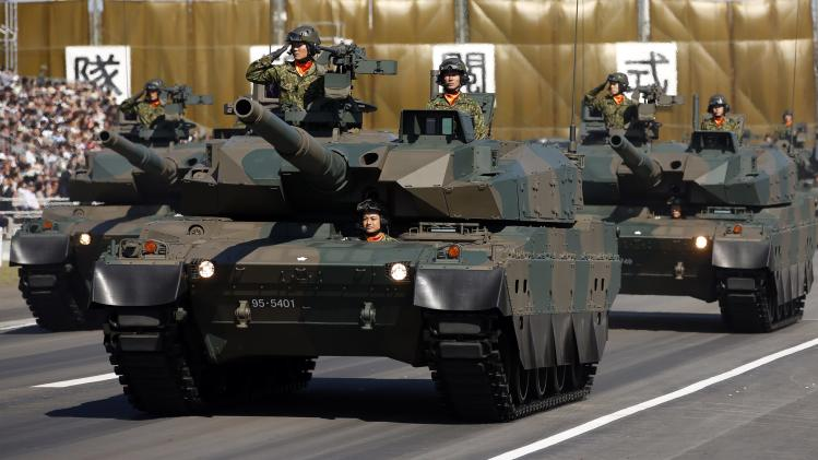 File photo of members of a tank unit of Japan's SDF riding on Type-10 armoured tanks takingpart in a military review during the annual troop review ceremony at Asaka Base in Asaka
