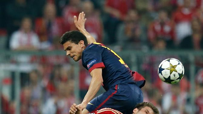 Barcelona's Marc Bartra, left, jumps on Bayern's Thomas Muller, a foul for which he was shown a yellow card, during the Champions League semifinal first leg soccer match between Bayern Munich and FC Barcelona in Munich, Germany, Tuesday, April 23, 2013. (AP Photo/Matthias Schrader)