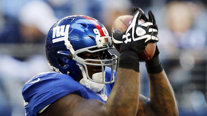 New York Giants defensive end Jason Pierre-Paul (90) intercepts a pass intended for Dallas Cowboys running back Felix Jones (28) during the first half of their NFL football game, Sunday, Oct. 28, 2012, in Arlington, Texas. The Giants won 29-24. (AP Photo/The Waco Tribune-Herald, Jose Yau)