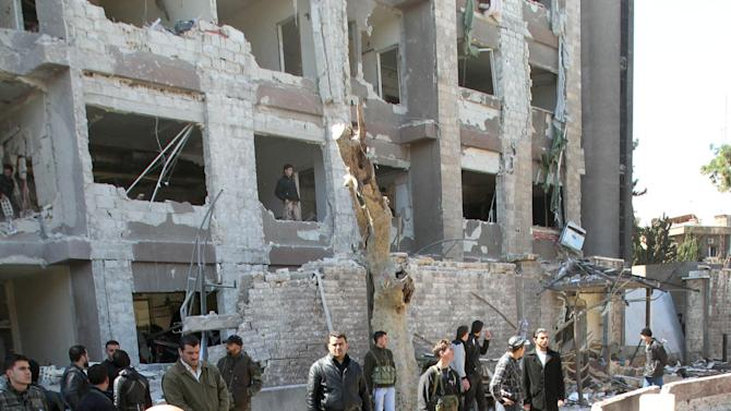 Syrian security officers gather next to a bomb crater in front the damaged building of the aviation intelligence department, which was attacked by one of two explosions, in Damascus, Syria, on Saturday, March 17, 2012. Twin bombings struck government targets in the Syrian capital early Saturday, killing security forces and civilians and leaving pools of blood and carnage in the streets, according to state-run television. (AP Photo/Bassem Tellawi)