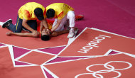 China's Lin Dan lies on the ground as he is congratulated by his coaches after winning his men's singles badminton gold medal match against Malaysia's Lee Chong Wei at the London 2012 Olympic Games at the Wembley Arena August 5, 2012.                 REUTERS/Bazuki Muhammad (BRITAIN  - Tags: SPORT BADMINTON SPORT OLYMPICS TPX IMAGES OF THE DAY)