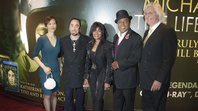 Lawyers Susan Yu, left, and Thomas Mesereau Jr, right, join producer David Gest, 2nd from left, Rebbie and Tito Jackson, 2nd from right, after their arrival for the European Premiere of Michael Jackson: The Life Of An Icon, at a central London cinema, Wednesday, Nov. 2, 2011. (AP Photo/Joel Ryan)