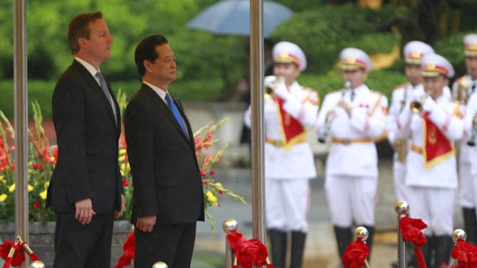 Britain's Prime Minister David Cameron and his Vietnamese counterpart Nguyen Tan Dung listen  to their national anthems during a welcoming ceremony at the Presidential Palace in Hanoi
