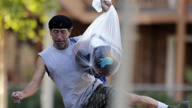 """Roberto Martinez hops over the police tape as he carries his belongings from his home near the apartment of alleged gunman James Holmes Friday, July 20, 2012 in Aurora, Colo. Authorities report that 12 died and more than three dozen people were shot during an assault at the theatre during a midnight premiere of """"The Dark Knight."""" Colorado firefighters are monitoring the Aurora apartment building for gases in an effort to determine what chemicals they say 24-year-old James Holmes might have used to trap the place _ in case the materials go off. (AP Photo/Alex Brandon)"""